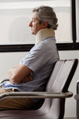 Man With Neck Injury Resting In Lobby — Stock Photo