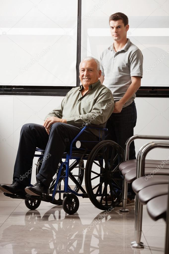 Portrait of young man with his grandfather on wheelchair in hospital lobby — Stock Photo #18237521
