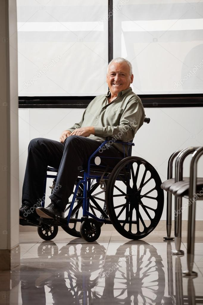 Portrait of happy senior man on wheelchair in hospital lobby — Stock Photo #18237673