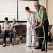 Man Being Helped By Nurse To Walk Zimmer Frame - Stock Photo