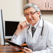 Doctor Sitting At Desk In Front Of Computer — Stock Photo #18240699