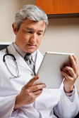 Doctor Looking At Digital Tablet — Stock Photo