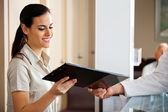 Receptionist Taking Clipboard From Doctor — Stockfoto