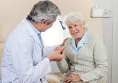 Doctor Comforting Senior Female Patient — Stock Photo