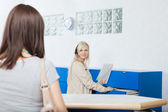 Receptionist Looks At Woman In Dentist's Office — Stock Photo