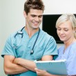 Young Female Nurse Showing Clipboard To Male Vet — Stock Photo
