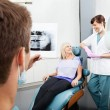 Stock Photo: Dentist Examining X-Ray Image With Female Assistant Communicatin