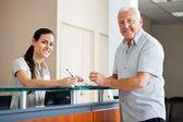 Senior man die bij de receptie van het ziekenhuis — Stockfoto