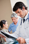Doctor Reading Document At Reception — Stock Photo