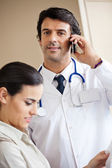 Doctor Answering Call While Standing With Colleague — Zdjęcie stockowe