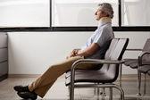 Homem com lesão no pescoço, esperando no lobby — Foto Stock