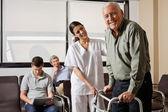 Sjuksköterskan att hjälpa äldre patient med walker — Stockfoto