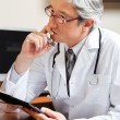 Thoughtful Doctor At Desk - Stock Photo