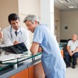 Stock Photo: Doctors Reviewing X-ray At Reception