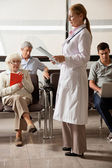 Doctor Reading File With In Lobby — Zdjęcie stockowe