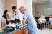 审查在接待处的 x 射线的医生 — 图库照片