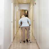 Woman With Walker In Corridor — Stock Photo
