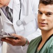 Male Technician With Doctor In Background - Stock Photo