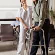 Female Nurse Helping Senior Patient With Walker - Stock Photo