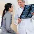 Radiologist Looking At Female Patient - Stock Photo