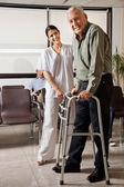 Female Nurse Helping Senior Patient With Walker — Stock Photo