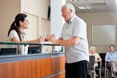 Hombre comunicarse con recepcionista femenino — Foto de Stock
