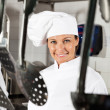 Female Chef With Spoons Hanging In Foreground — Stock Photo #21122883