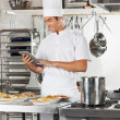 Happy Chef Using Digital Tablet In Kitchen — Stockfoto