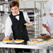 Stock Photo: Waiter And Chef Working In Commercial Kitchen