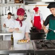 Chefs Working In Restaurant Kitchen - Stock Photo