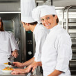 Stock Photo: Female Chef With Colleagues In Commercial Kitchen