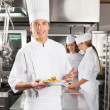 Confident Chef Presenting Dish In Commercial Kitchen — Stock Photo #21125513
