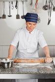 Chef féminin, rouler la pâte au comptoir de la cuisine — Photo