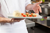 Chef Presenting Dish In Kitchen — Stock Photo