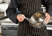 Male Chef Whisking Egg In Kitchen — Stock Photo