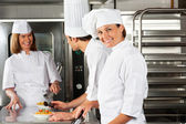 Female Chef With Colleagues In Commercial Kitchen — Stock Photo