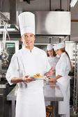 Confident Chef Presenting Dish In Commercial Kitchen — Stock Photo