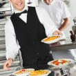 Waiter Holding Pasta Dish - Stock Photo