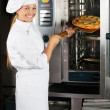 Female Chef Placing Pizza In Oven — Stock Photo