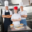 Stock Photo: Confident Chefs With Sweet Dishes On Kitchen Counter