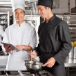 Chef Assisting Colleague In Preparing Food - Stock Photo