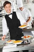 Waiter Holding Pasta Dish — Stock Photo