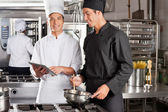 Chef Assisting Colleague In Preparing Food — Stock Photo