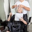 Royalty-Free Stock Photo: Woman Reading Magazine While Having Haircut
