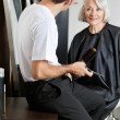 Stock Photo: Hairdresser Examining Customer's Hair At Parlor