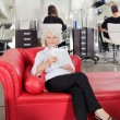 Woman Reading Magazine With Clients Waiting For Hairdresser — Stock Photo