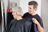 Hairdresser Removing Client's Apron After Haircut — Stok fotoğraf