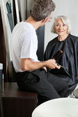 Hairdresser Examining Customer's Hair At Parlor — Stock Photo