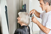 Hairstylist Straightening Customer's Hair — Stock Photo