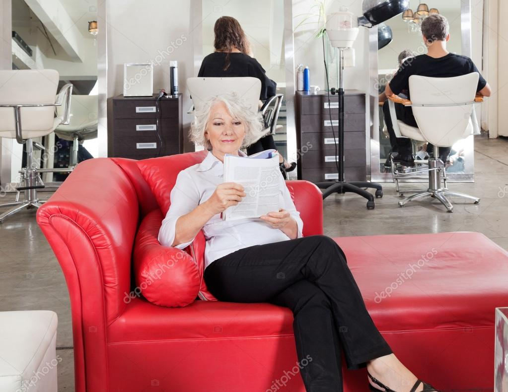 Woman reading magazine with clients waiting for for Reading beauty salon